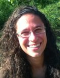 Devra Goldstein headshot with green bushes in the background.