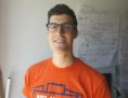 Gabriel Fontes headshot. Gabriel is wearing an orange T shirt, with a flipchart in the background.