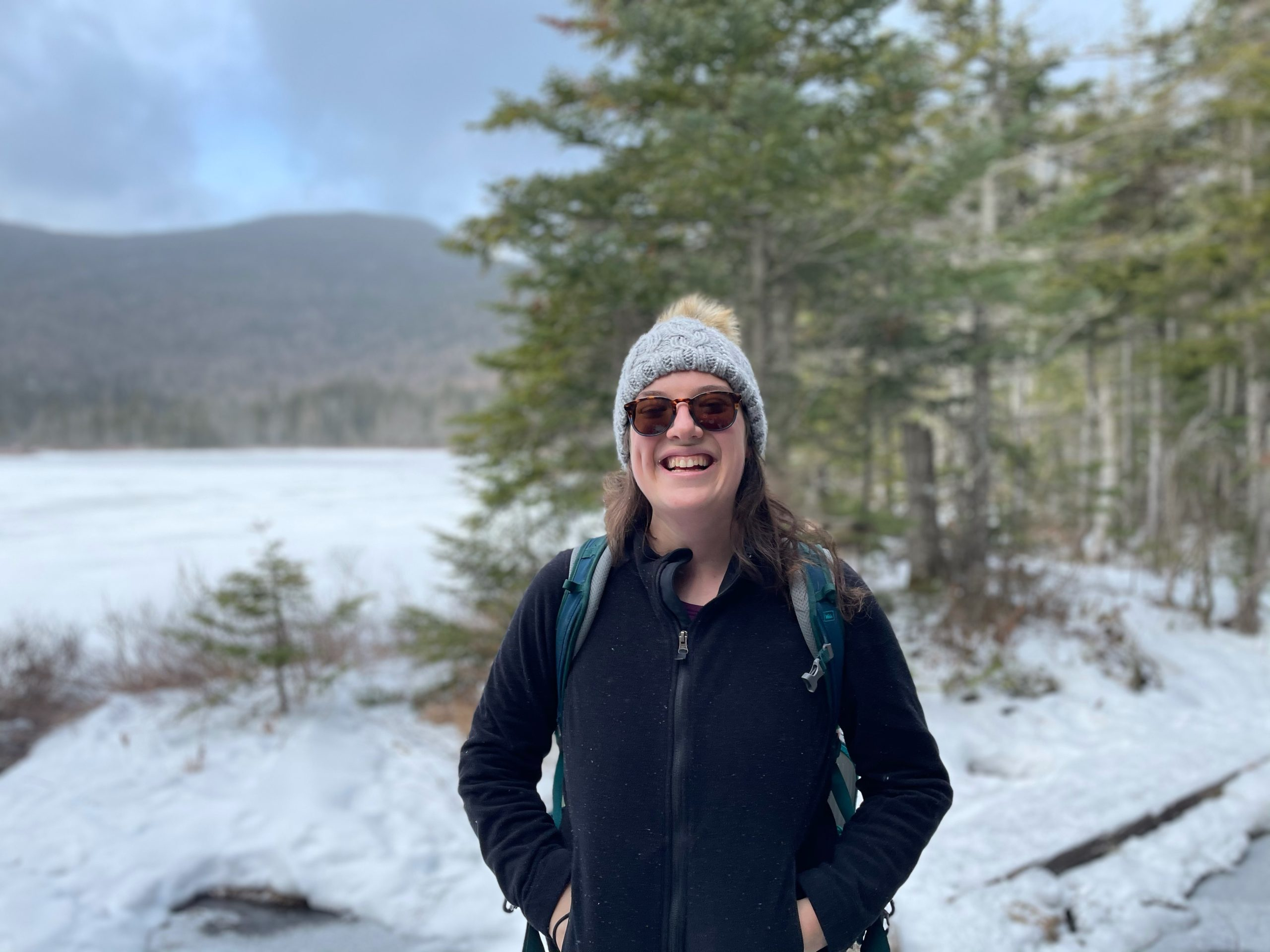 photo of Eviva Kahne standing outside where snow, trees, and a distant mountain can be seen