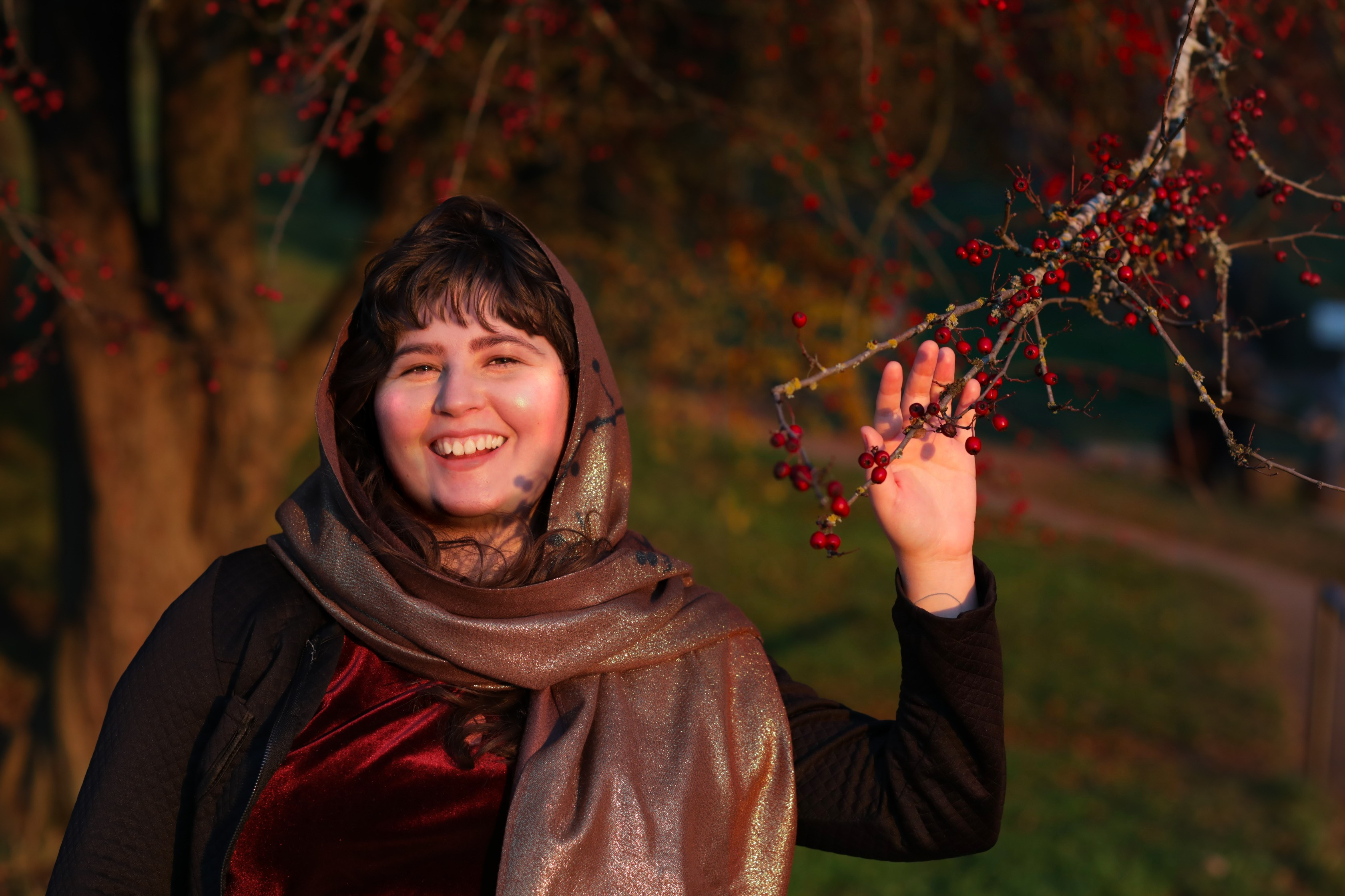 photo of Sahar L. Jones in front of a tree with the hand reaching for a branch with red berries