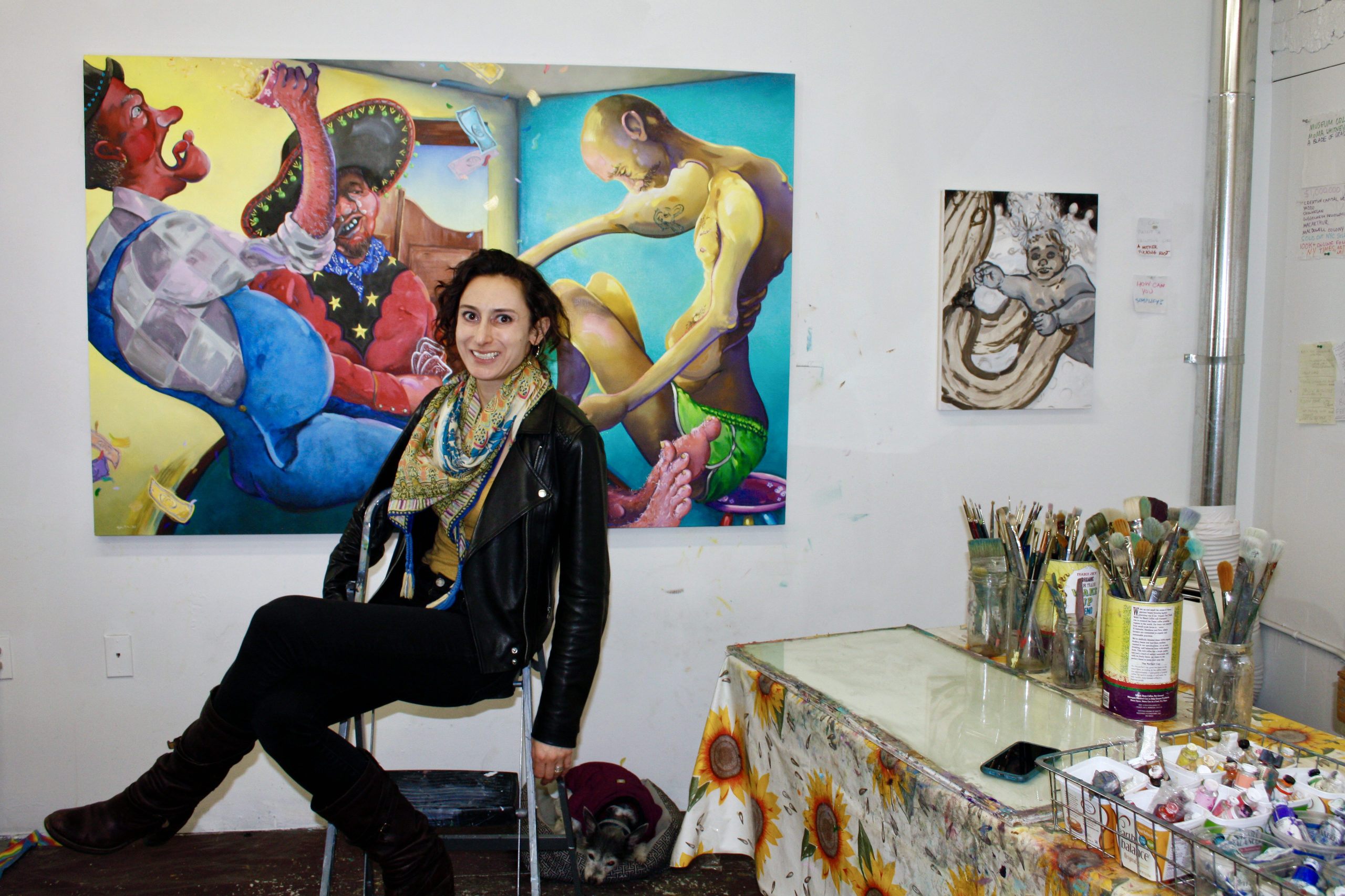 photo of Samantha Fein in front of a colorful painting with art supplies, a table and a smaller painting also in view