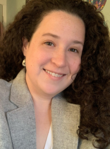 Headshot of Caitlin Brazner, white woman, curly brown hair to shoulders, smiling, grey blazer with silver drop-earrings.