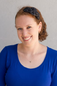 photo of Emily Holtzman, a white women with auburn hair in a blue top and black flower headband
