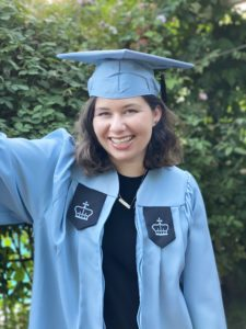 photo of Noa Rubin, a brown shoulder length haired short white woman in a blue graduation cap and gown, smiling with teeth