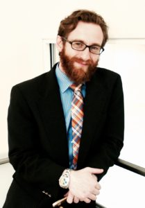 professional photo of Will Guyster at the Massachusetts Institute of Technology, white man in a jacket and tie, short reddish hair and beard, glasses, leaning on a stairwell.