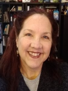 Headshot of Edie smiling, a white woman with blue eyes, red hair and wearing a grey shirt with sweater
