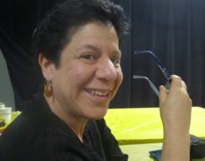 Headshot of Leah smiling, holding her glasses, wearing gold earrings; short black hair and hazel eyes.