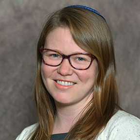 Headshot of Maddy smiling. A white woman with hazel eyes and tortoiseshell glasses, strawberry blonde hair with a blue kippah, and wearing a grey shirt with a white sweater sweater.